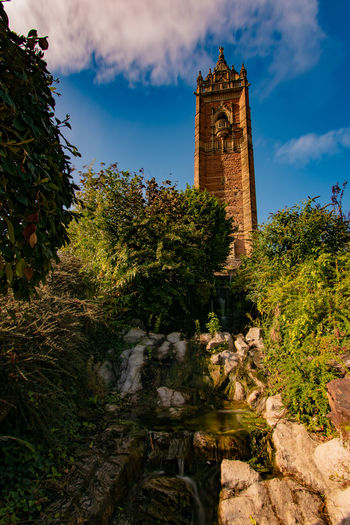 Low angle view of clock tower amidst trees and buildings against sky