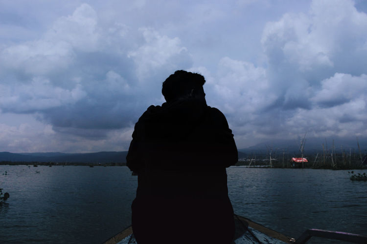 Rear view of silhouette man in river against sky