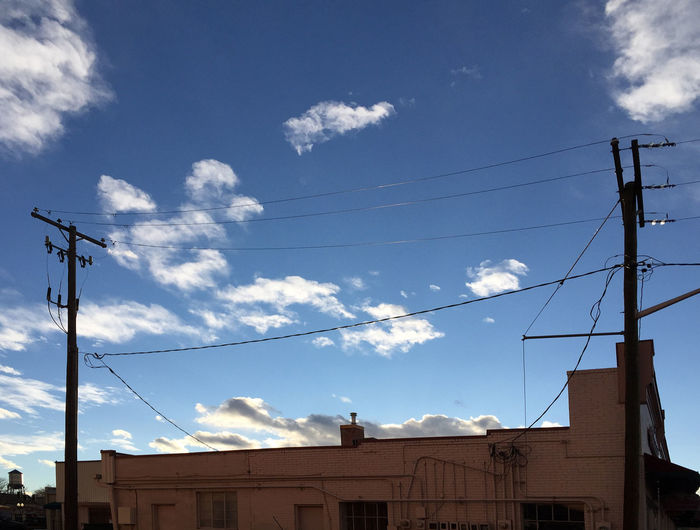 Clouds and power poles in Denver CO Architecture Blue Building Building Exterior Built Structure Cable Cloud Cloud - Sky Colorado Day Denver Denver,CO Electricity  Low Angle View No People Outdoors Pole Power Cable Power Line  Power Supply Sky United United States
