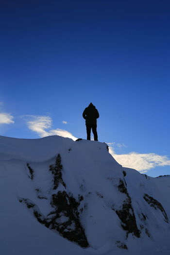 Silhouette man standing on snow covered landscape against blue sky
