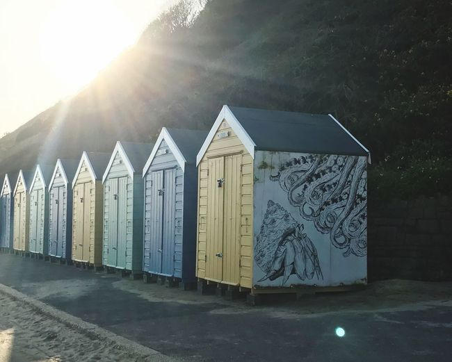 Huts for days Mural Graffiti Art Beach Sunlight No People In A Row Nature Sky Lens Flare Security Architecture Day Built Structure Wood - Material Outdoors
