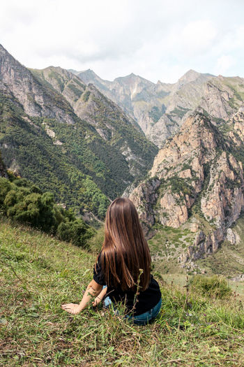 Rear view of woman sitting against mountains