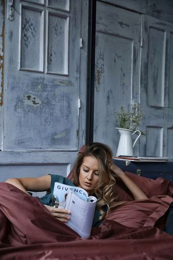 Girl in bed reading a magazine One Person Lying Down Bed Real People Leisure Activity Lifestyles Bedroom Front View Book Relaxation Indoors  Full Length Day Young Women Young Adult People
