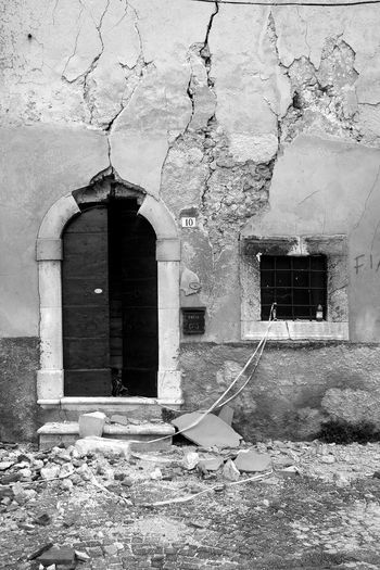 L'Aquila earthquake: damaged building facade with door and window Rubble Wall Arch Architecture Black And White Blackandwhite Building Exterior Built Structure Damaged Building Door Doorway Earthquake Earthquake In Italy Earthquake L'aquila Entrance House Open Door Outdoors Ruined Building Window
