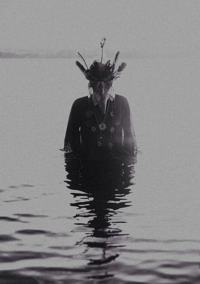 Person wearing bizarre costume standing in lake