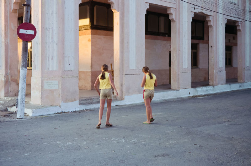 Full length of a man with woman walking in front of building