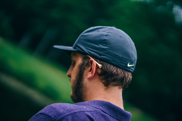 Golf Player Looking Downwards Golf Golf Course Golfing Sportsman Adult Beard Blue Cap Casual Clothing Clothing Club Course Game Golfer Headshot Leisure Activity Lifestyles Looking Away Men Outdoors Rear View Score Sport Sports Sports Photography