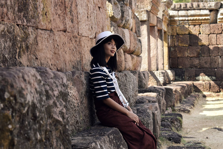 Young pretty asian girl sits on the foundation of an ancient hindu temple ruins