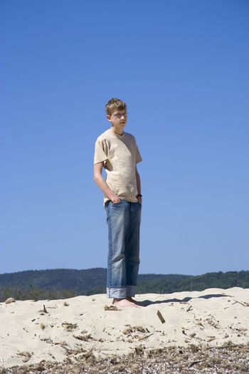 Full length of young man standing with hands in pockets on sandy beach against clear blue sky