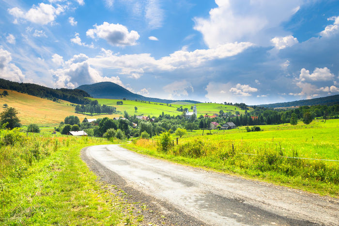 Road, village and mountain summer landscape Agricultural Land Day Field Field Green Hill Landscape Meadow Natural Nature No People Nobody Outdoor Photography Poland Scenery Sky Spring Summer Sunny Town Travel Tree Valley View Way