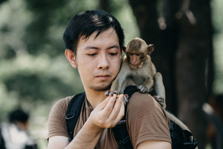 Monkey taking food from man while sitting on his shoulder
