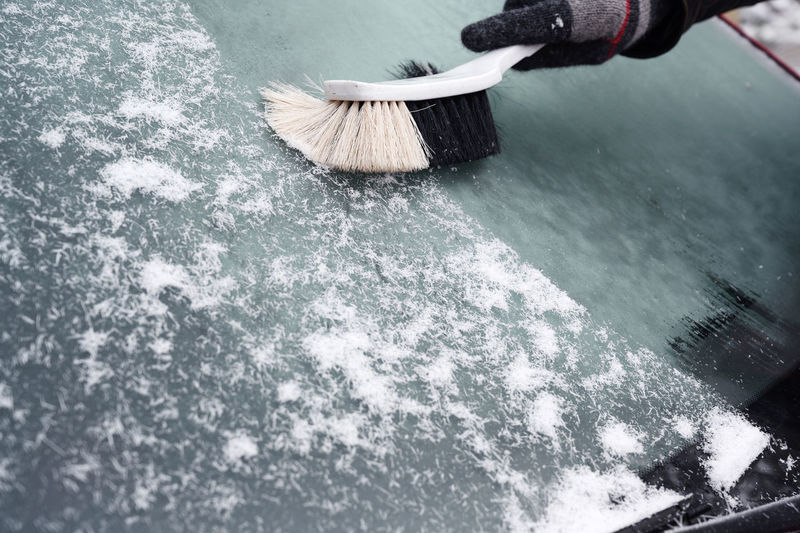 hand broom sweeps the snow from the windshield of a car in winter, copy space Car Traffic Snow Broom Hand Sweeping Cleaning Winter Windshield Danger Safety Driving Season  Transportation Day Outdoors Copy Space Frost Ice Human Body Part Cold Temperature Tool Nature
