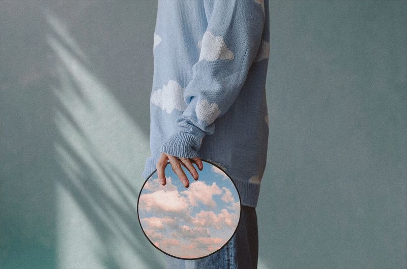 A man with a mirror in his hands reflecting the sky
