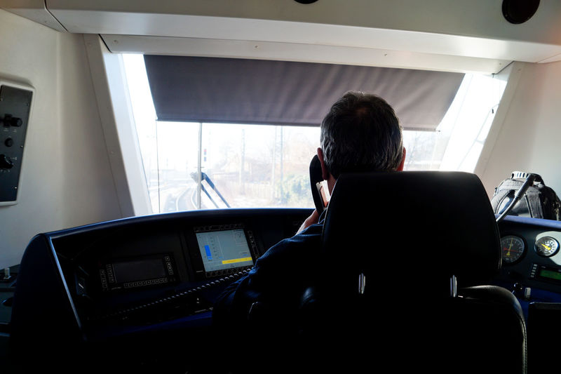 Rear view of man sitting in cockpit of train