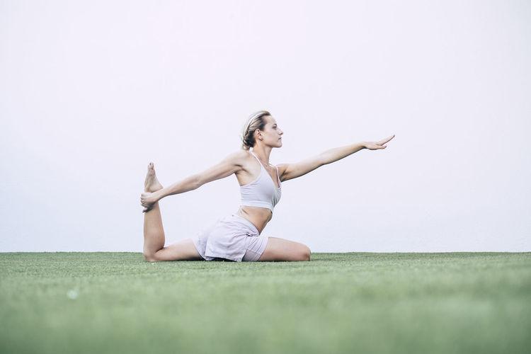 Full length of woman exercising on field against sky