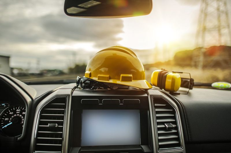 Close-up of hardhat on dashboard in car against sky