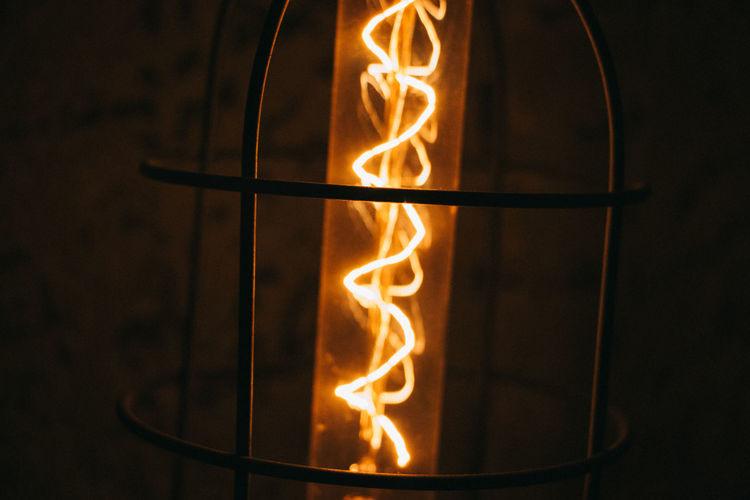 Close-Up Of Illuminated Lantern Against Wall