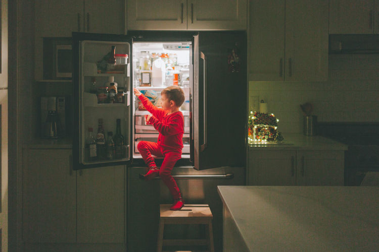 Full length of boy taking food from refrigerator in kitchen at home