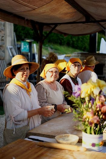 Women in medieval clothes impaste bread Adult Women Medieval Festival Clothes Medieval Impastey Breads Food Handmade Work