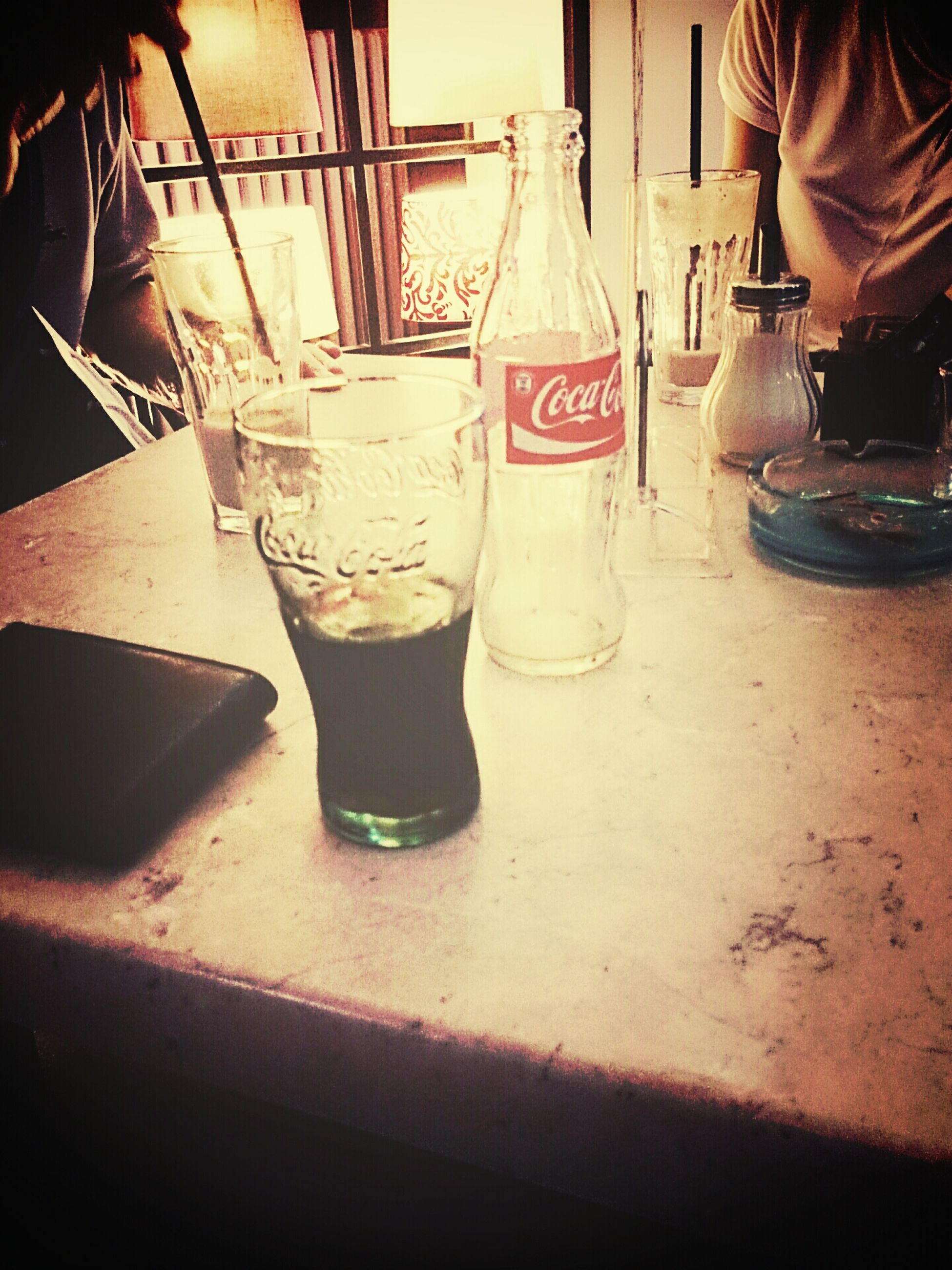 drink, food and drink, table, refreshment, drinking glass, indoors, restaurant, glass - material, freshness, close-up, incidental people, sunlight, beach, focus on foreground, alcohol, text, lifestyles, water