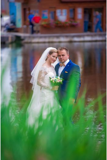 Portrait of bride and groom posing together against lake