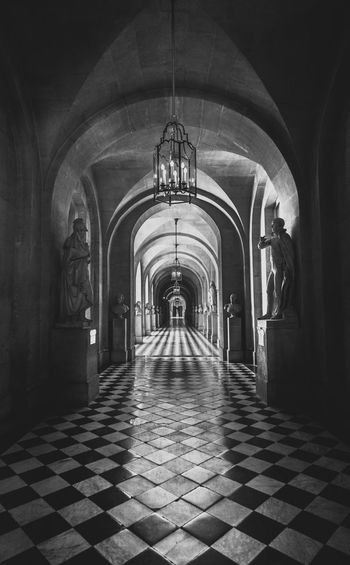 Black white photography of inside architecture of castle Versailles in France. Kings House Hotel Versailles Versailles Gardens Arcade Arch Architectural Column Architecture Building Built Structure Ceiling Corridor Diminishing Perspective Direction Electric Lamp Flooring Illuminated Indoors  Lighting Equipment monochrome photography No People Place Of Worship Spirituality The Way Forward Tile Tiled Floor