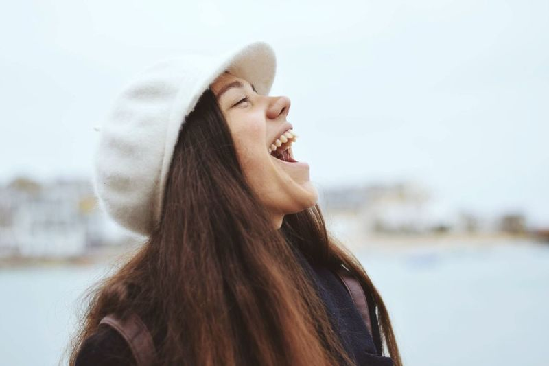 Woman laughing against sky