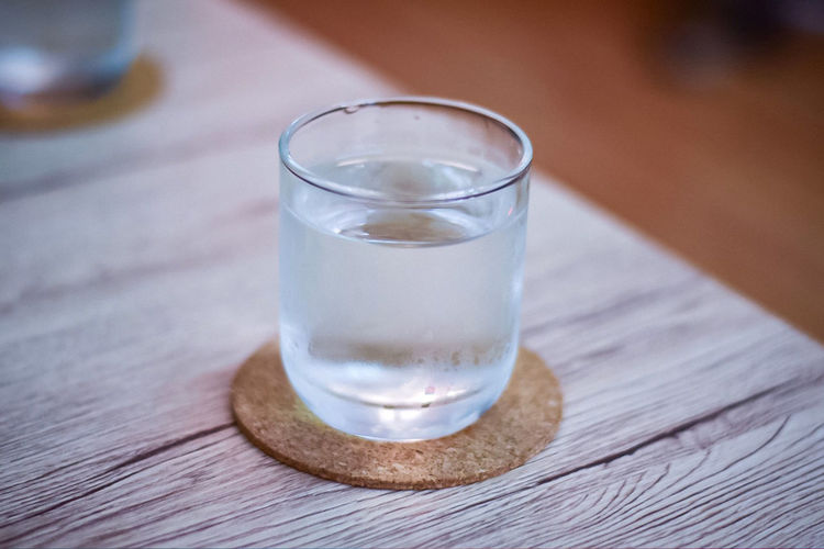 One glass of water Glass Drinking Glass Household Equipment Table Drink Refreshment Food And Drink Water Drinking Water Focus On Foreground Close-up Indoors  Wood - Material Transparent No People Freshness Glass - Material Cold Temperature Purity
