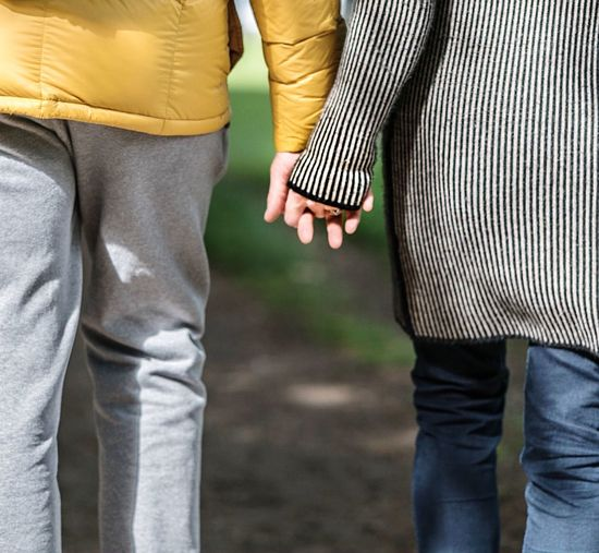 Midsection of couple holding hands while standing at park