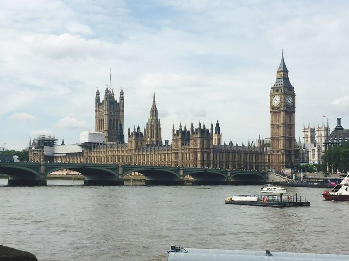 House of parliament in front of thames river against cloudy sky