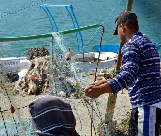 Fishing Net Casual Clothing Catch Of Fish Day Fish Fisherman Fishermen Fishermen's Life Fishing Fishing Boat Fishing Industry Fishing Net Holding Leisure Activity Marine Men Nature Nautical Vessel One Person Outdoors Real People Sea Three Quarter Length Transportation Water