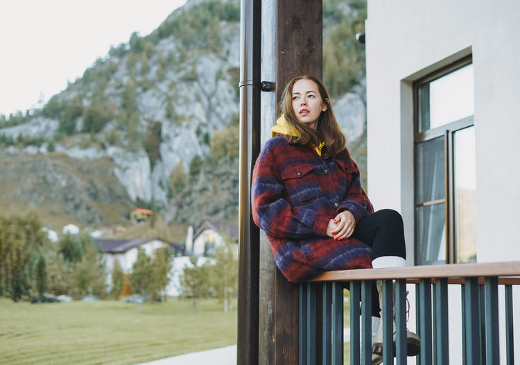 Young woman in coat sitting on wooden fence near cottage on mountains background