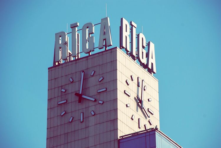 Clock tower of Riga train station Clock Tower Latvia Riga Train Station Architecture Building Exterior Built Structure Clear Sky Sky Low Angle View Blue Text No People Building Tower Outdoors Communication Western Script City Day Sunlight