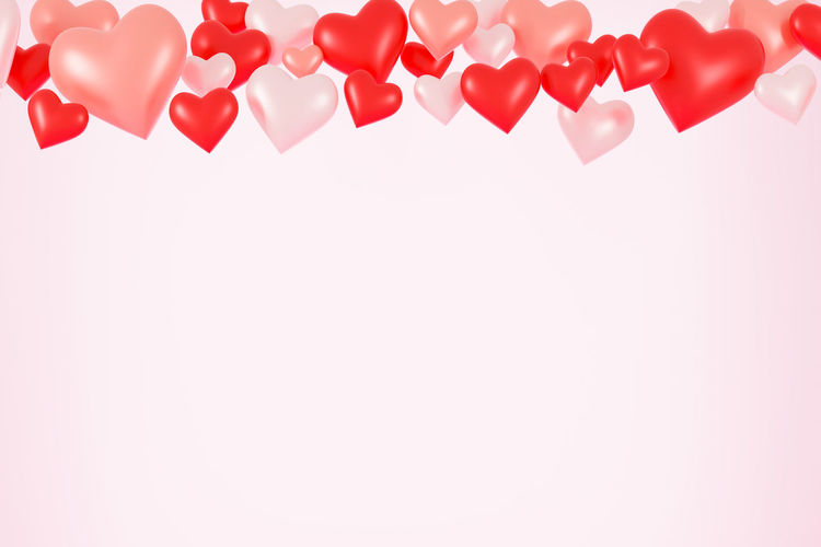 Heart shape made of multi colored balloons against white background