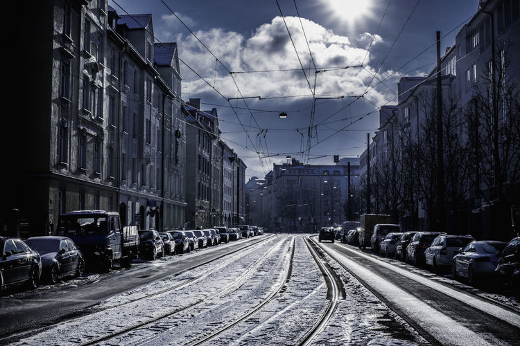 Vehicles Parked On Snow Covered Street Amidst Buildings Against During Winter