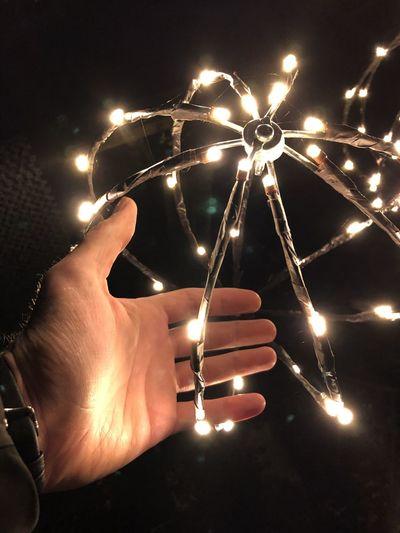 Close-up of hand holding illuminated lights at night