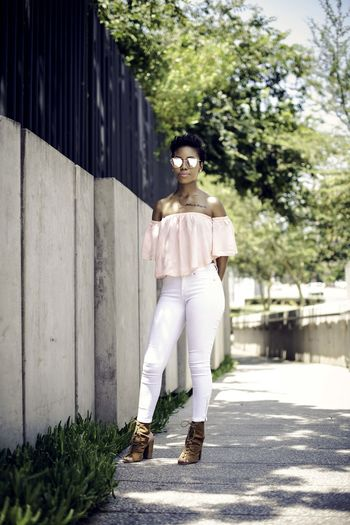 Young Woman Wearing Sunglasses Standing On Footpath By Concrete Fence