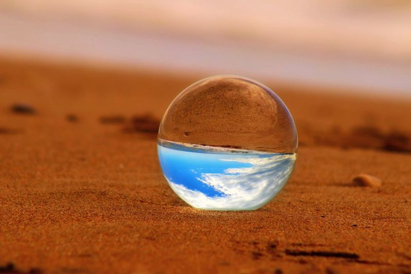Close-up of crystal ball on sand