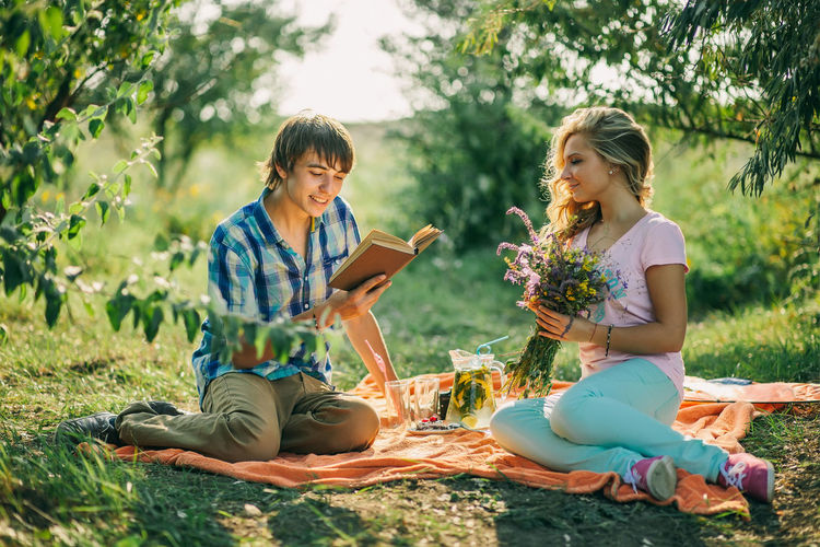 Man Reading Book By Woman On Field