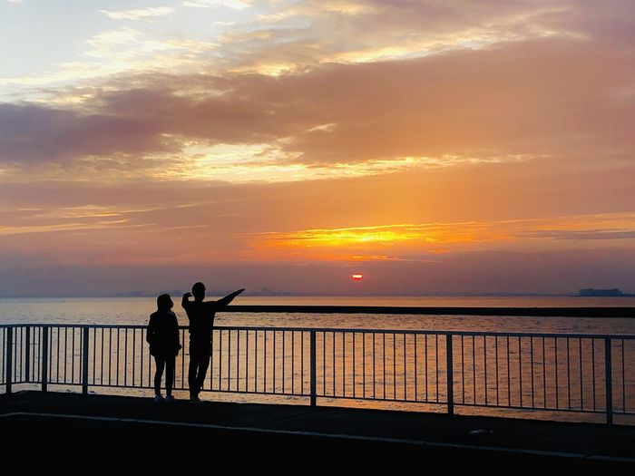 Silhouette people standing by railing against sea during sunset