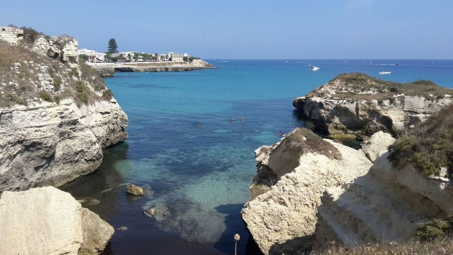 Cliffs in sea against clear sky at salento