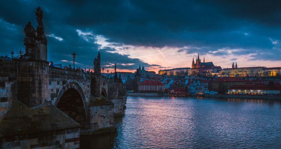 View Of Prague Waterfront Against Cloudy Sky
