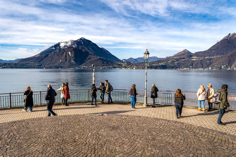 Tourists standing on observation point by lake against mountains during sunny day