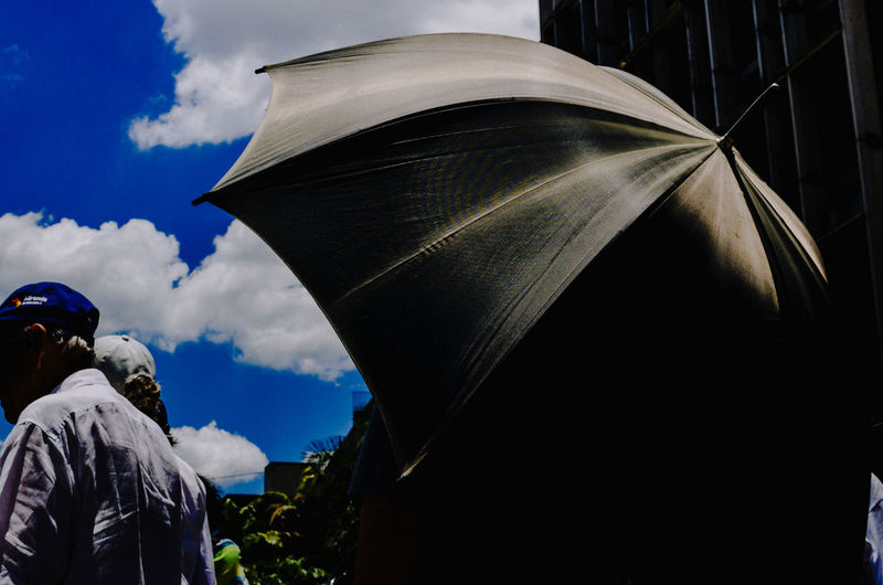 Marching Out Umbrellas EyeEm Best Shots EyeEm Selects Sky Cloud - Sky Art And Craft Representation Nature Architecture Sculpture Human Representation Rear View Real People People Creativity Men Statue Day Built Structure Outdoors Male Likeness Spirituality Sunlight Street Streerphotography Street Photography