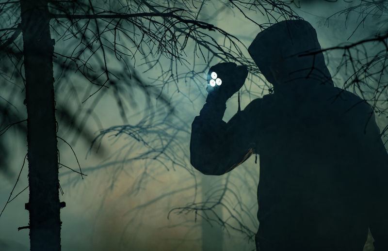 Silhouette man holding flashlight standing by tree in forest at night
