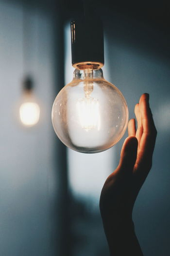 Cropped image of person touching illuminated light bulb