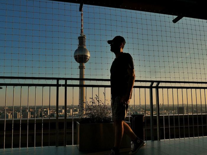 Silhouette man walking by railing against fernsehturm during sunset