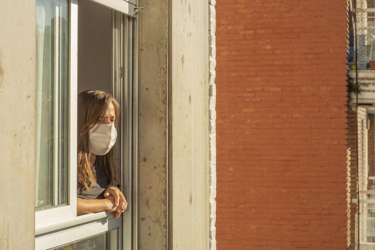 Woman looking through window of door