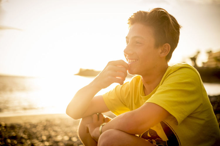 Close-up of teenage boy smiling while sitting at beach against sky during sunset