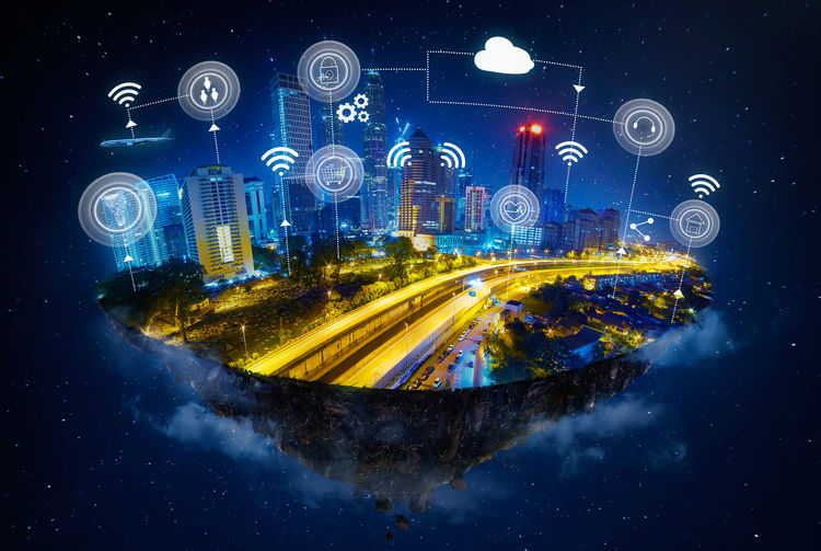 Composite image of illuminated city with various symbols against sky at night